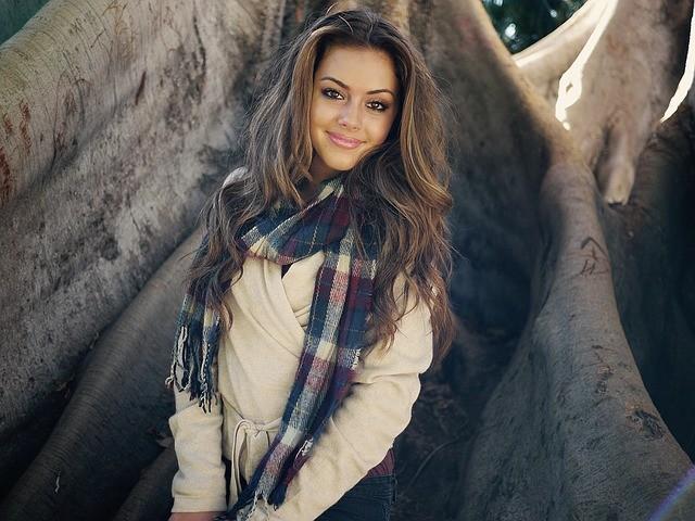 Femme souriante devant un arbre